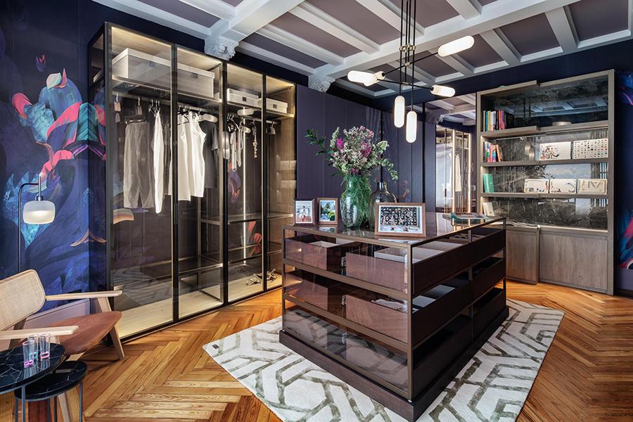 vestidor con armarios en madera y cristal con una isla central en madera oscura y alfombra