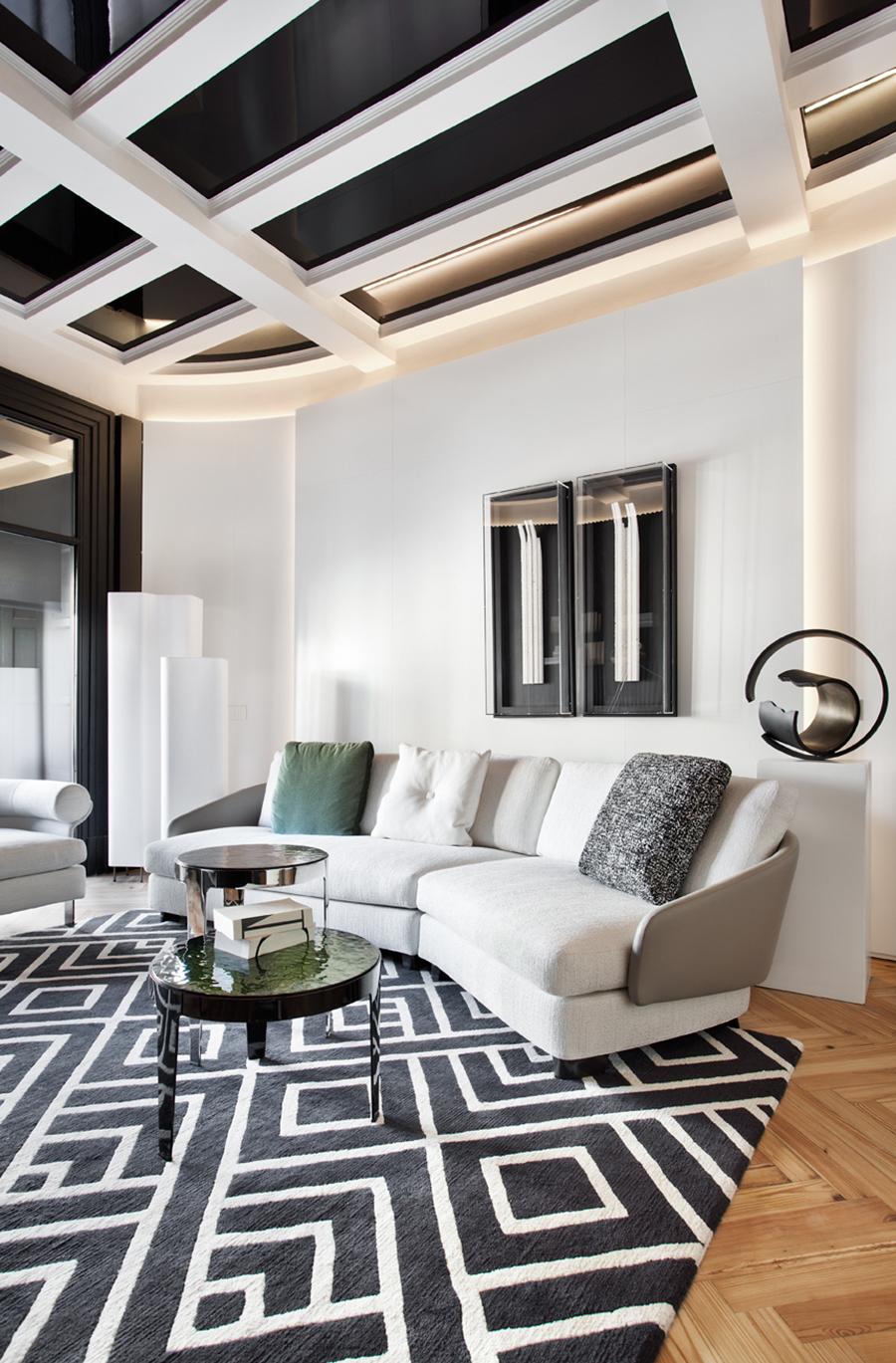 espacio amplio con sofá en gris claro y alfombra en blanco y negro. Detalles en verde y piezas decorativas artísticas