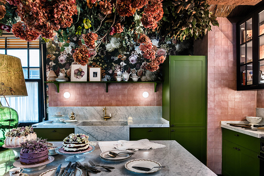 cocina con techo de flores y mobiliario en verde. Azulejos en rosa palo y encimera de mármol blanco