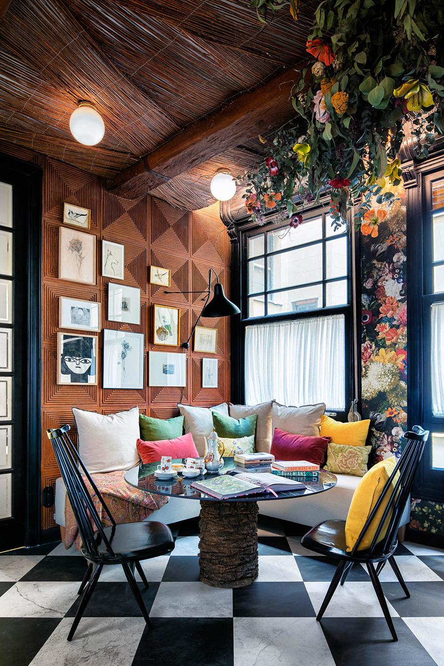 comedor con sofá más butacas con cojines coloridos. Techo floral e iluminación decorativa