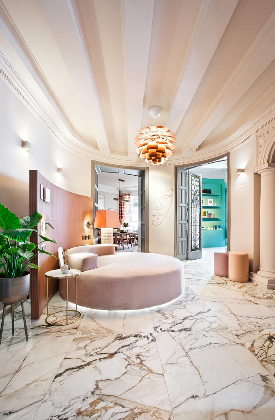 sala amplia con suelo de mármol y cama circular en rosa. lampara decorativa protagonista