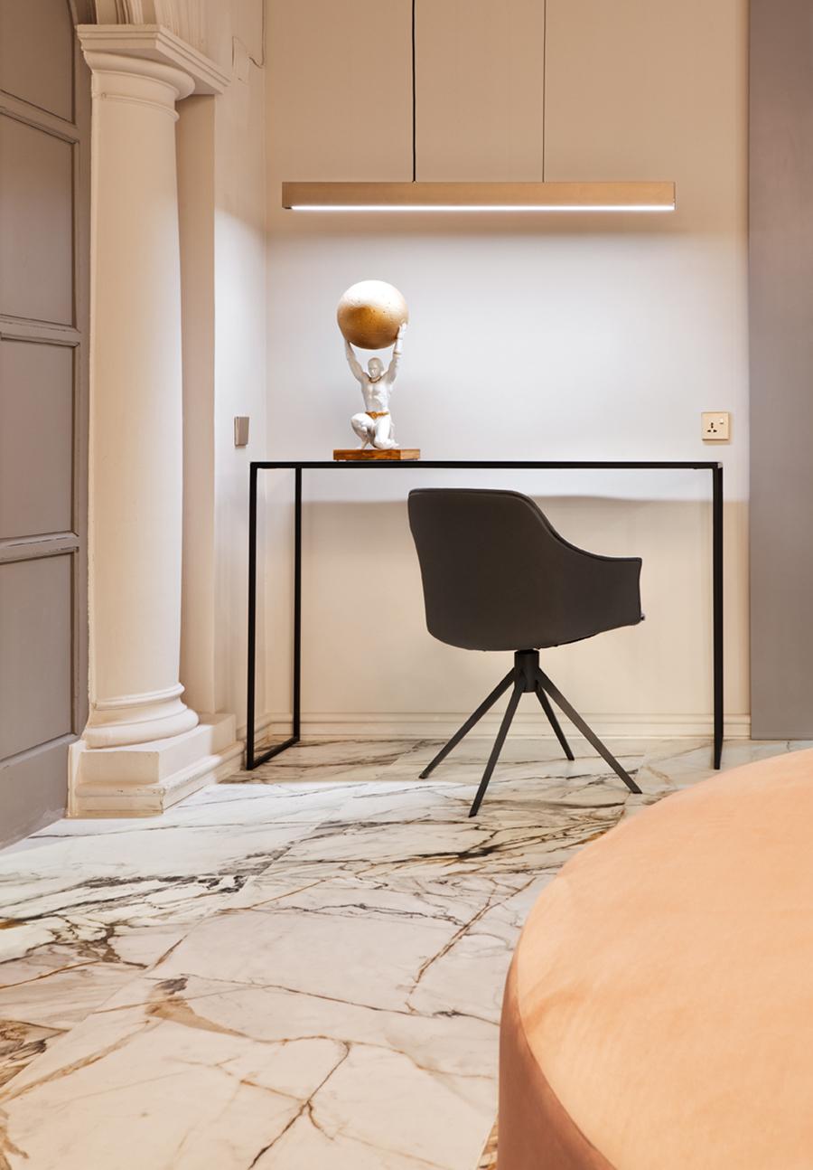 rincón con un mueble alto en negro junto a butaca gris oscuro. Lámpara recta de formas lineales