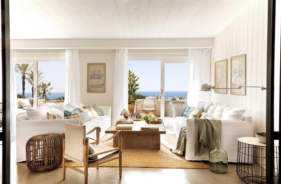 salón amplio de un apartamento de playa en tonos blancos con vistas al mar