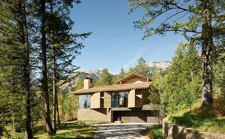 casa en la montaña en el bosque con fachada de piedra y madrea