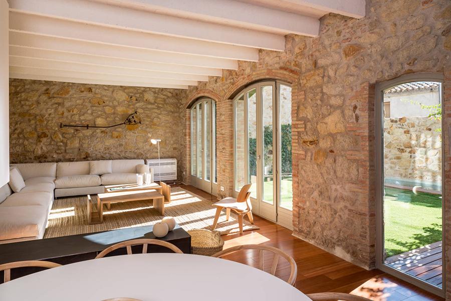 salón rústico con paredes de piedra vistas y decoración neutra